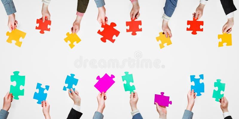 Différents morceaux réglés de puzzle dans des mains de personnes images libres de droits