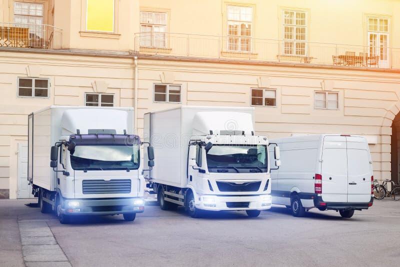 Différents petits et moyens camions et fourgon de messagerie à la cour de bâtiment Vehilcles de société de transports maritimes d photographie stock