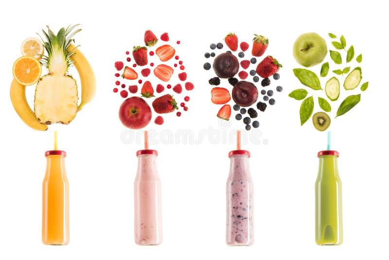 Différents smoothies sains dans des bouteilles avec les ingrédients frais d'isolement sur le blanc photos libres de droits