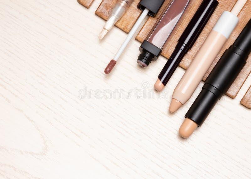 Différents types de crayons correcteurs de maquillage sur la table en bois blanche images libres de droits