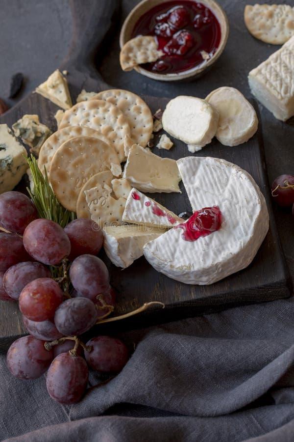 Différents types de fromage avec du raisin sur le conseil en bois images stock