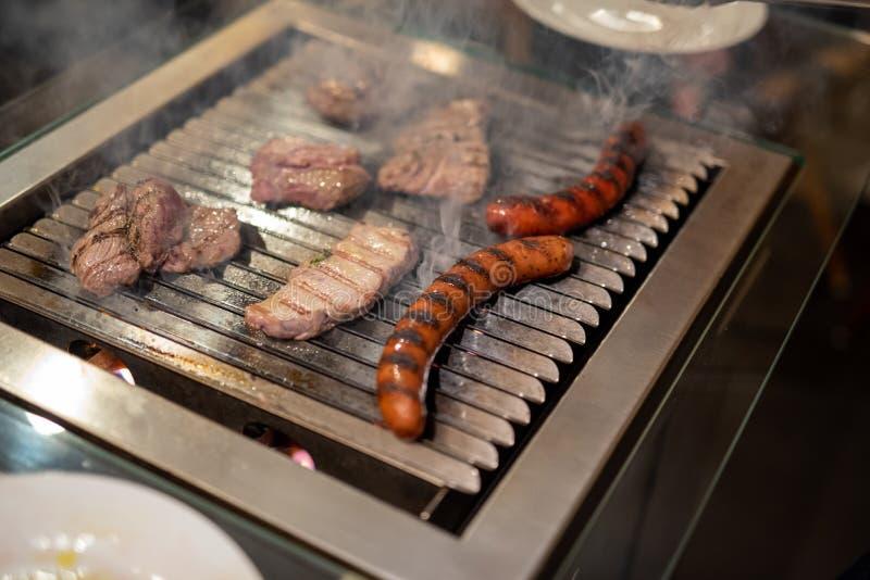 Diff?rents types de la viande, des biftecks de boeuf et de saucisses de proc, cuits sur un gril images stock