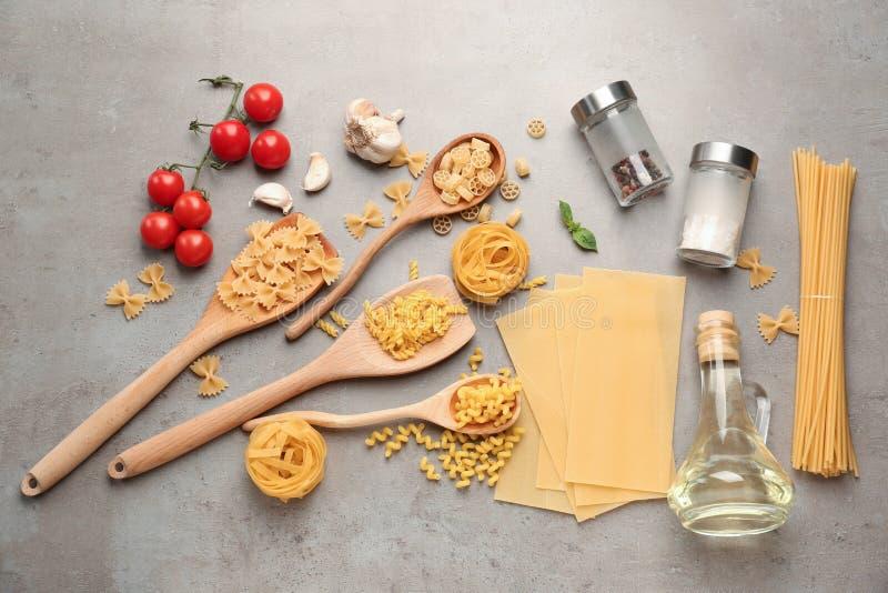 Différents types de pâtes crues avec des légumes et des épices sur la table grise images stock