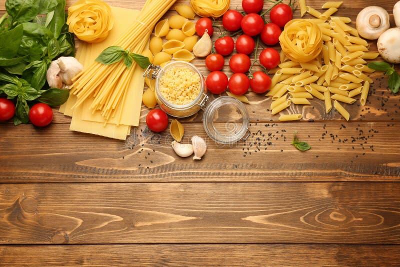 Différents types de pâtes crues avec des légumes sur la table en bois image stock