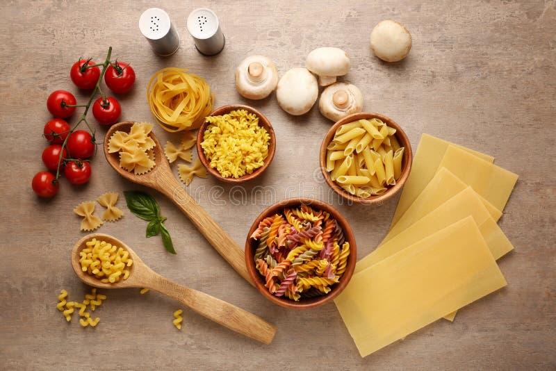 Différents types de pâtes crues avec des légumes sur le fond en bois photos libres de droits