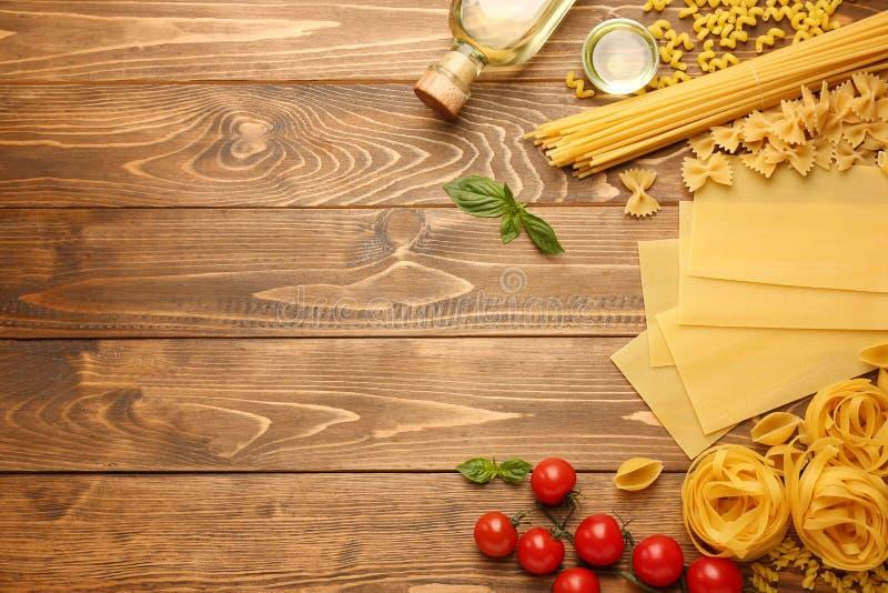 Différents types de pâtes crues avec de l'huile sur le fond en bois image libre de droits