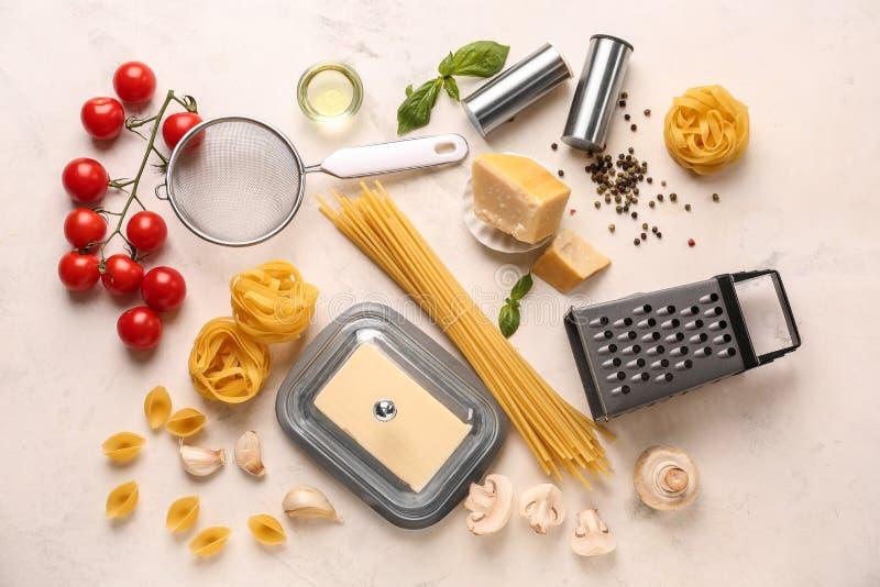 Différents types de pâtes crues avec les légumes et le fromage sur la table légère image libre de droits