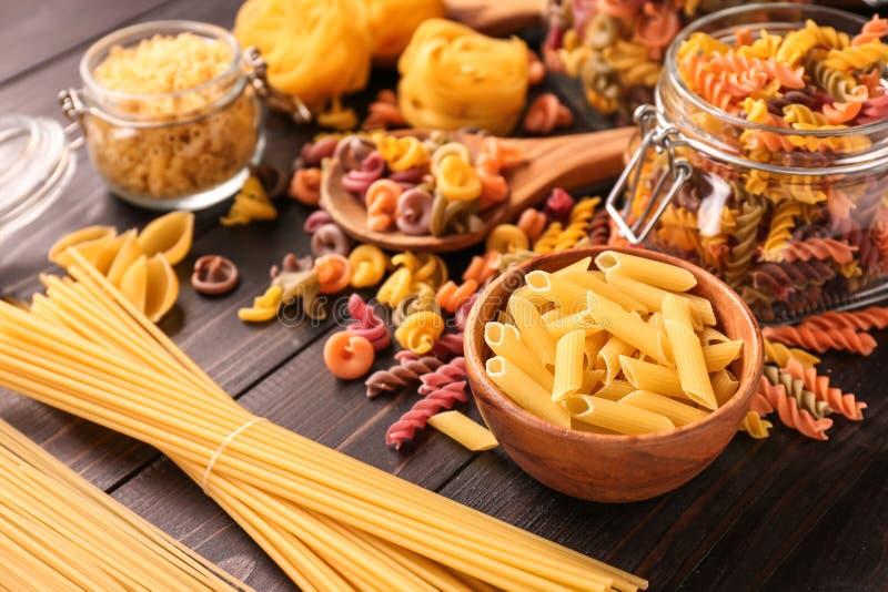 Différents types de pâtes crues sur la table en bois images stock