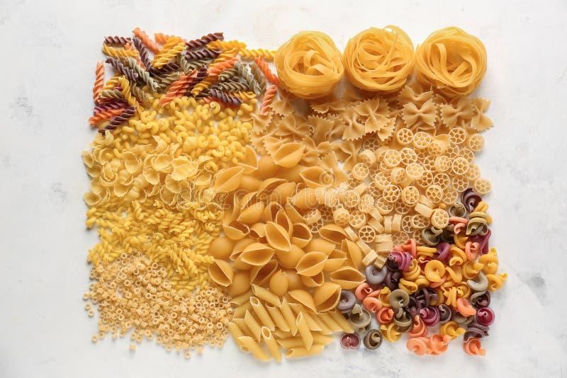 Différents types de pâtes crues sur le fond clair image stock