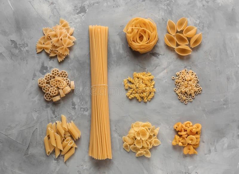 Différents types de pâtes crues sur le fond gris image stock