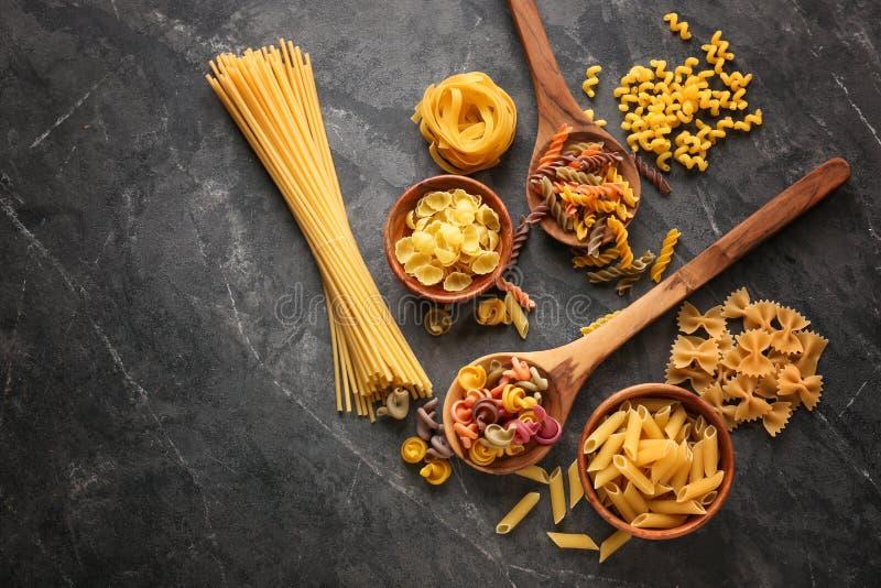 Différents types de pâtes crues sur le fond gris images stock