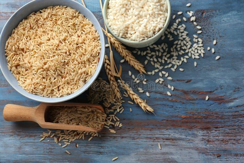 Différents types de riz dans des cuvettes et le scoop sur la table en bois images libres de droits
