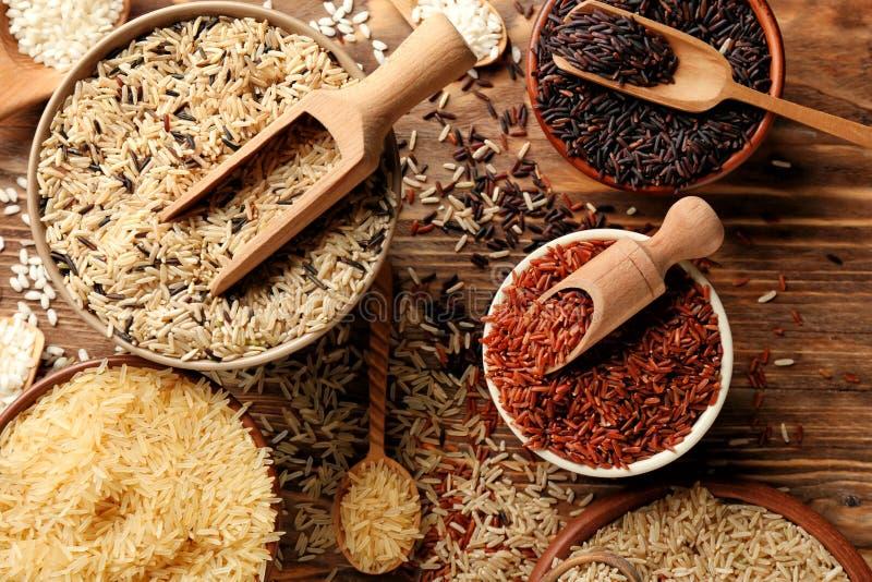 Différents types de riz dans des cuvettes sur la table en bois images stock