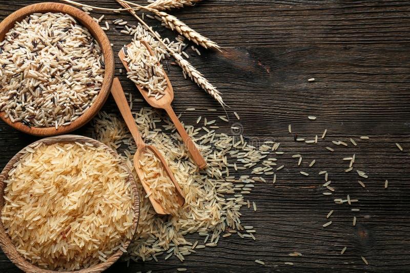 Différents types de riz dans la vaisselle de cuisine sur la table en bois photo stock
