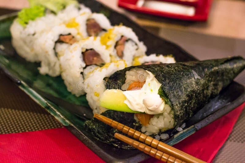 Différents types de sushi, saumons (épicés), avocat, fromage de philadephiia et riz blanc enveloppés dans l'algue photo stock
