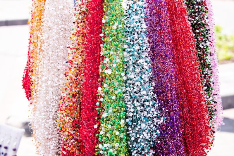 Diff?rents colliers de diverses formes et couleurs avec les pierres color?es sur un fond brouill? image stock
