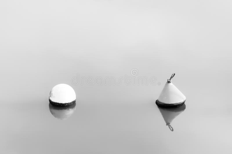 Difference. Concept. buoys floating on water. Black and white royalty free stock photo