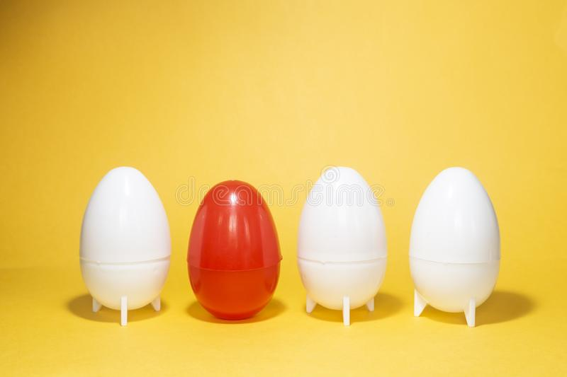 Difference concept. Four eggs on yellow. One red and three white plastic eggs. On yellow background stock photo