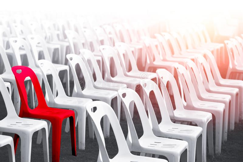 Difference red color chair unique outstanding person concept. Difference red color chair around with many white chairs for unique outstanding person concept stock image