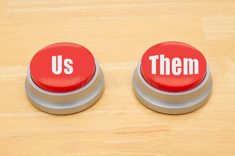 The difference between us and them. Two red and silver push button on a wooden desk with text Us and Them stock photography