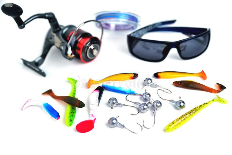 Different accessories for fishing, glasses, silicone bait, reel, braid, hooks isolate. Different accessories for fishing, glasses, silicone bait, reel, braid royalty free stock photography