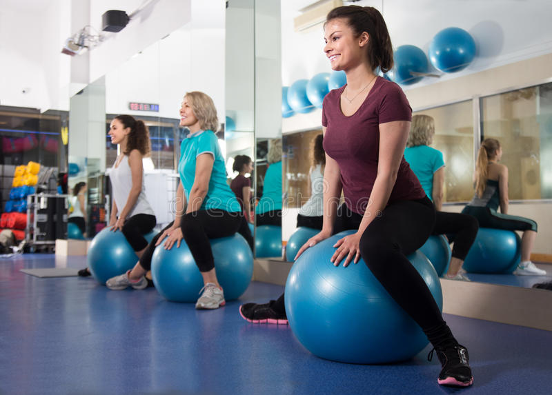 Different age women jumping on exercise ball during group train. Different age female jumping on exercise ball during group train in gym royalty free stock photography
