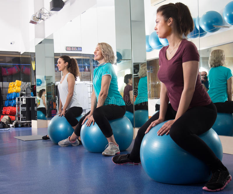 Different age women jumping on exercise ball during group train. At gim royalty free stock image