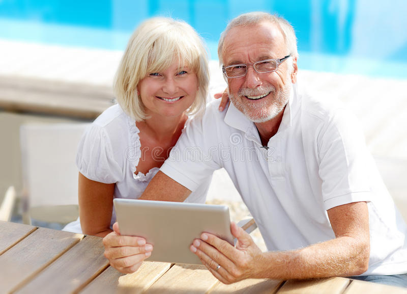 Different aged couple using a tablet pc outside royalty free stock photography
