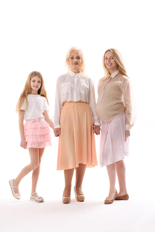 Different aged smiling female persons. Happy grandmother is standing between her daughter and grandchild. They are holding hands, looking at camera with smile royalty free stock image
