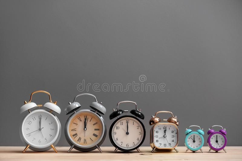 Different alarm clocks on wooden table against grey background stock photo