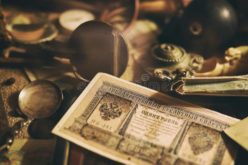 Different antique items on the table: bronze jewelry, banknotes and coins of the Russian Empire, glasses in a case, silverware. Vintage background from royalty free stock images