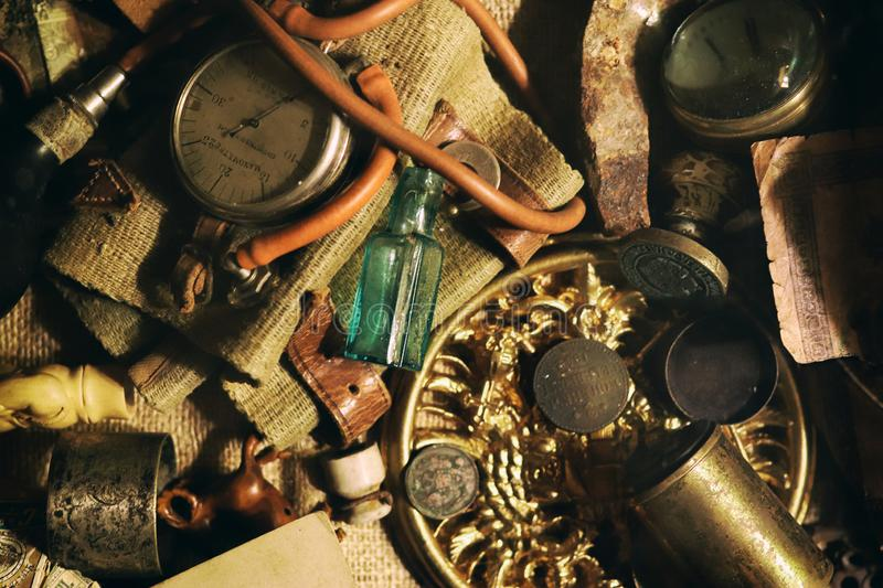Different antique items on the table: bronze jewelry, old money, retro manometer, magnifier, glass bottle, silverware. Vintage. Background from a collection of stock photography