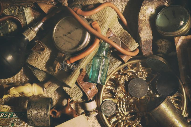 Different antique items on the table: bronze jewelry, old money, retro manometer, magnifier, glass bottle, silverware. Vintage. Background from a collection of stock image