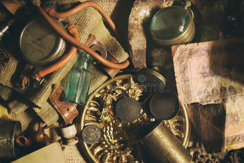 Different antique items on the table: bronze jewelry, old money, retro manometer, magnifier, glass bottle, silverware. Vintage. Background from a collection of royalty free stock image