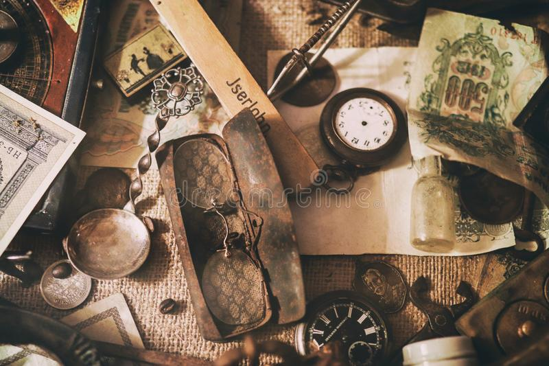 Old pocket watches, banknotes and coins of the Russian Empire, glasses in a case, silverware. Different antique items on the table: old pocket watches, banknotes royalty free stock photography