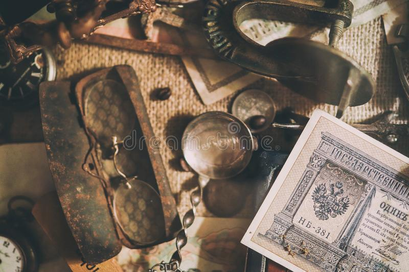 Different antique items on the table: old pocket watches, banknotes and coins of the Russian Empire, glasses in a case, silverware. Vintage background from a stock photos