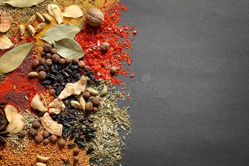 Different aromatic spices on dark background, top view. With space for text royalty free stock images