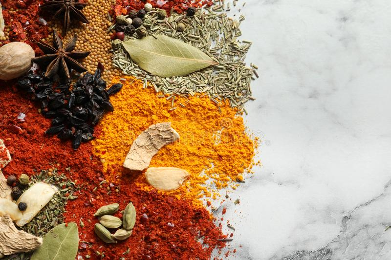 Different aromatic spices on marble background, top view. With space for text royalty free stock images