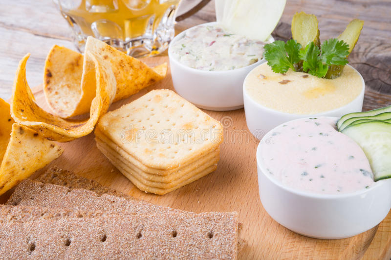 Different beer snacks. Crackers with hummus served on wooden board stock images