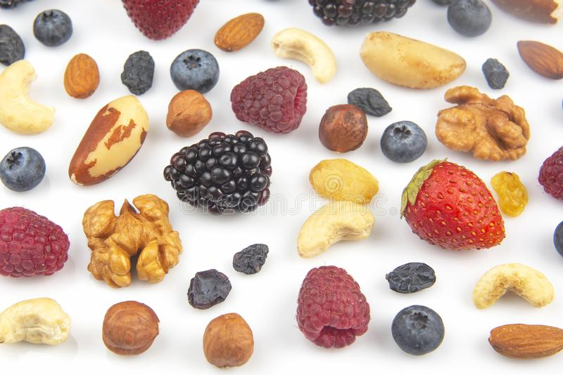 Different berries and nuts on a white background. vitamin proteins and healthy foods. The different berries and nuts on a white background. vitamin proteins and royalty free stock image