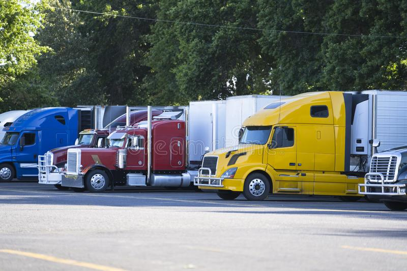 Different big rigs semi trucks with semi trailers standing in row on truck stop. Popular big rigs semi trucks of different makes and models standing in row on royalty free stock photo