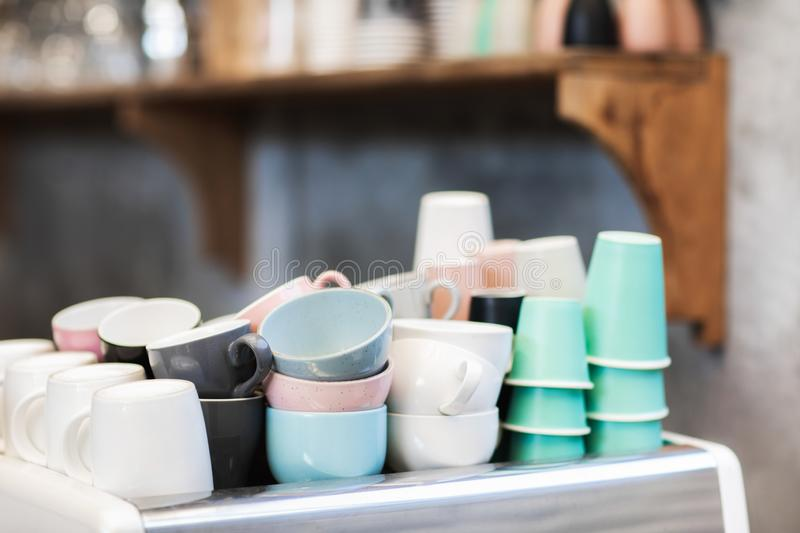 Different blue, pink, white and green cups in cafe stock images