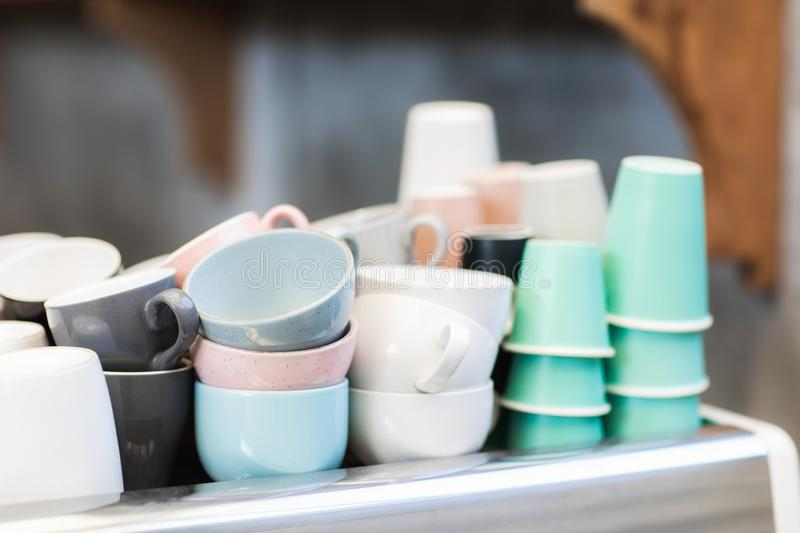 Different blue, pink, white and green cups in cafe. Heap of different blue, pink, white and green cups on coffee machine in cafe. Barista concept. Background of stock images
