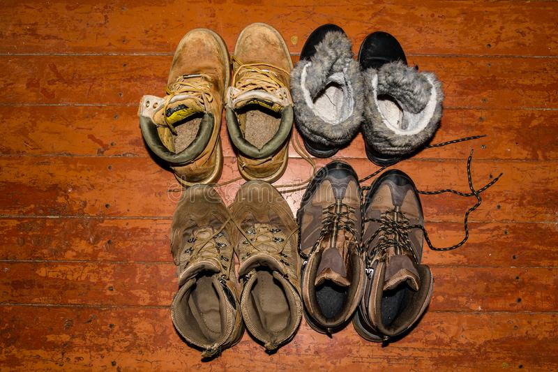 Different boots on a rustic wooden floor. Top view royalty free stock photography