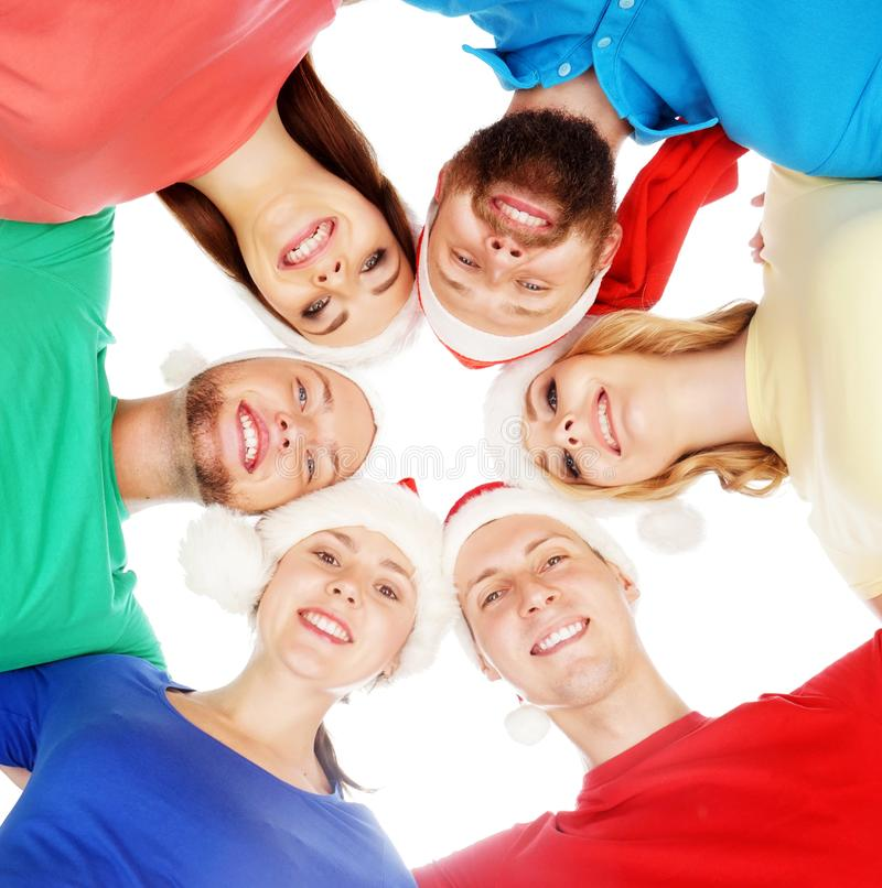 Different boys and girls in Christmas hats embracing together isolated on white. royalty free stock image