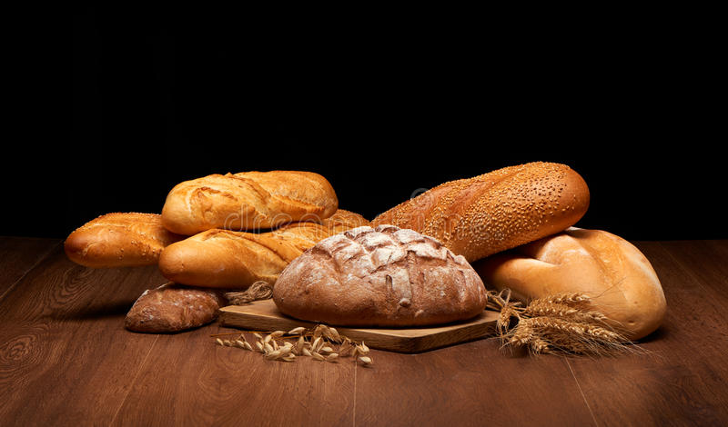 Different bread and wheat on dark wooden table stock photography