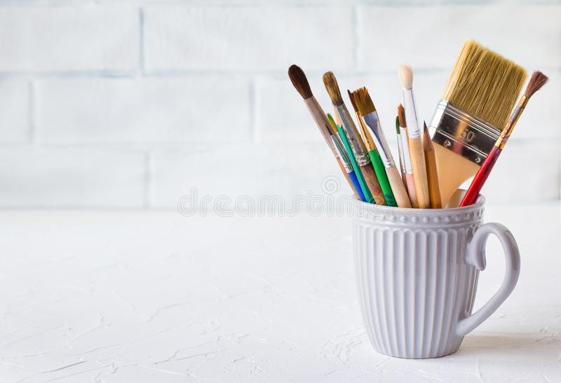 Different brushes in a gray mug on a white table against the background of a brick wall. stock photos