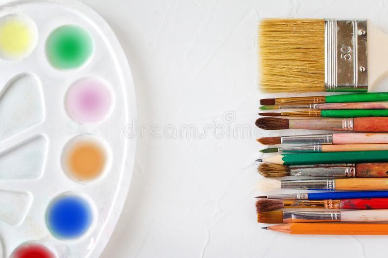 Different brushes, palette and pencils on a white surface. Art and education object. Copy space. Top view. royalty free stock image