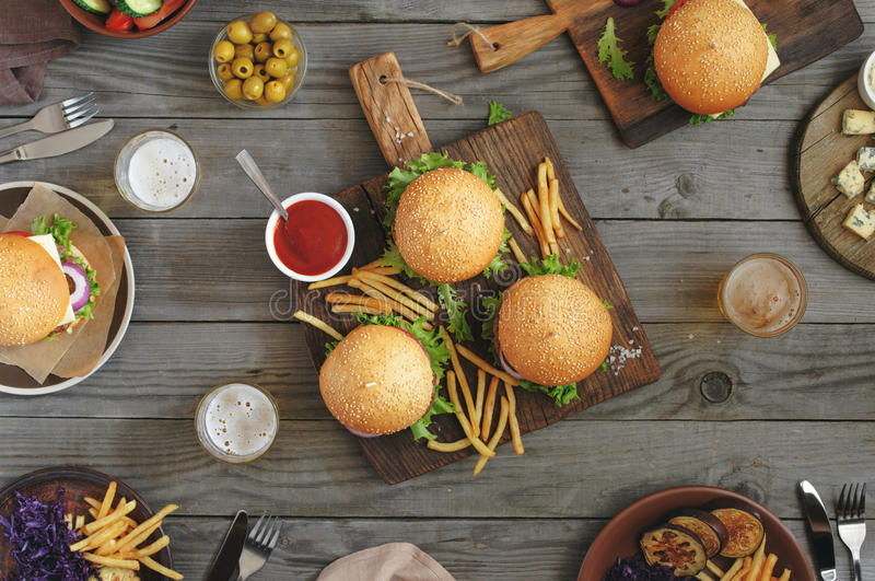 Different burgers with snacks and beer stock photography