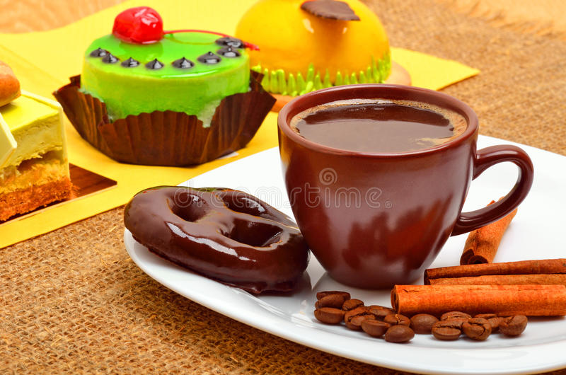 Different cakes, cup of coffee, cinnamon sticks and chocolate co. Okies on white plate on sacking background royalty free stock image